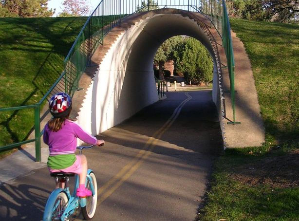 Boise River Greenbelt Tunnel With Child Riding Bike Towards It During Summer
