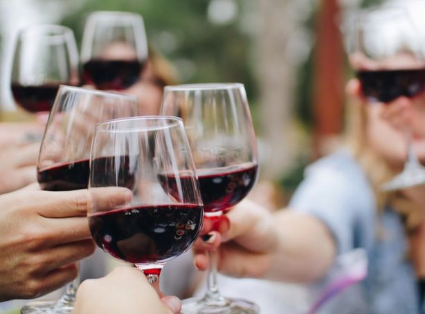 People Toasting Half-full Wine Glasses At An Outdoor Venue