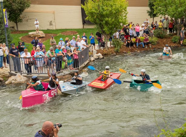 Cardboard Kayaks race down the river as an audience watches