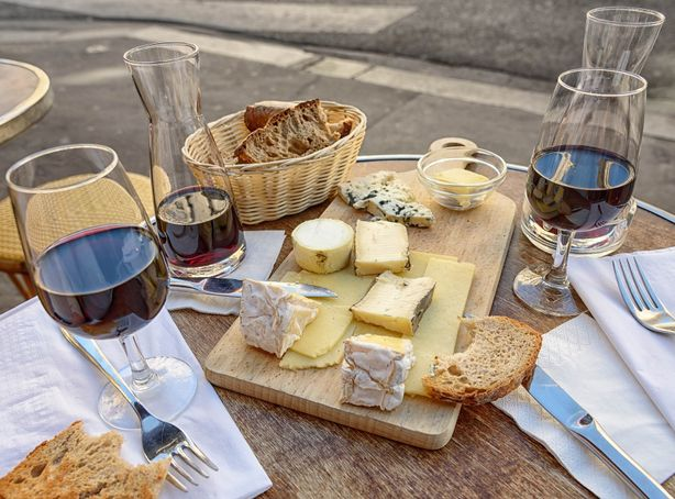 A table for two is set with glasses of red wine, a cheese board and fresh bread.