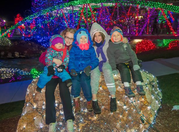 A smiling family poses for a photo amongst the outdoor festival lights