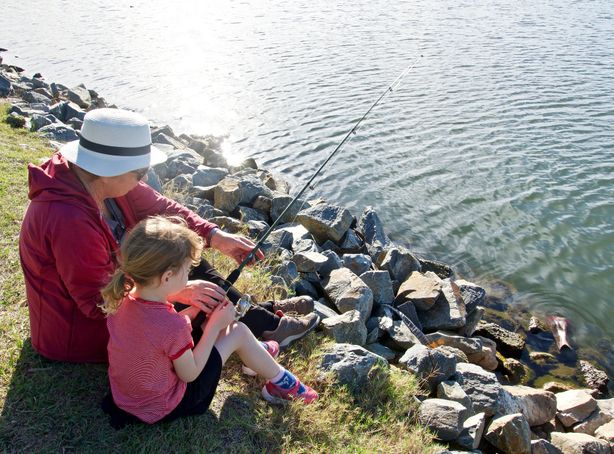 A woman and her granddaughter sit fishing from the banks of a small pond.