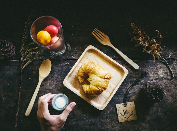 A buttery croissant accentuates its accompanying dark wood table