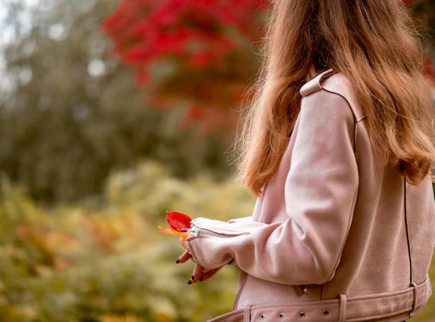 A woman holds red and orange leaves that have fallen off a nearby tree