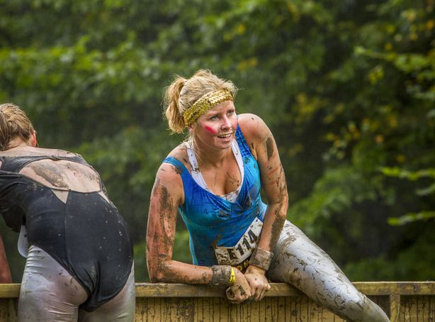 Runners climb over a wall obstacle during an annual mud run race