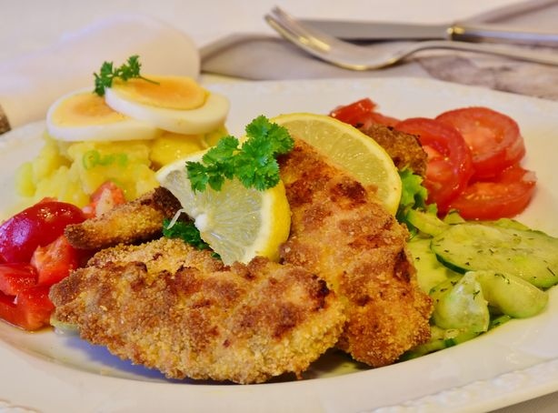 A large cut of schnitzel sits on a plate surrounded by vegetables