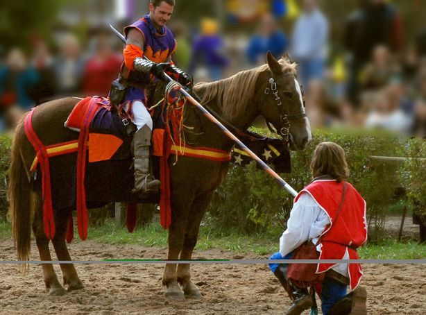 A squire helps prepare a knight on horseback for an upcoming jousting match