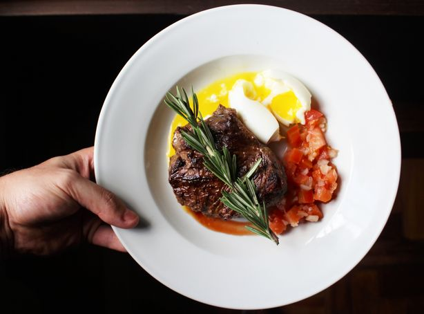 An artisanal steak dish with sides of diced tomatoes and soft boiled eggs.
