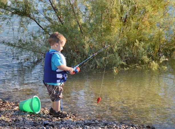 A small boy stands on the side of a pond fishing with a child's fishing rod