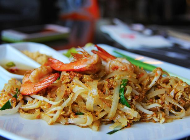 A portion of Pad Thai with large shrimp on a white plate